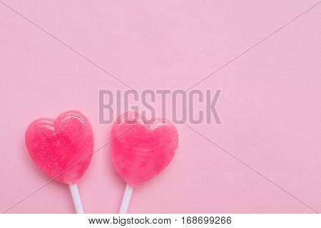 Two Pink Valentine's Day Heart Shape Lollipop Candy On Empty Pastel Pink Paper Background. Love Conc