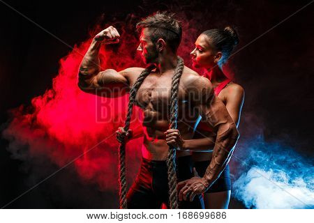 Two fit sportspeople posing together with big rope on man's neck.