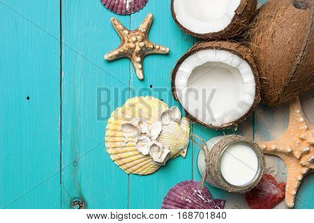 Fresh coconuts, coconut oil in a jar, shells and starfish on natural turquoise wooden background