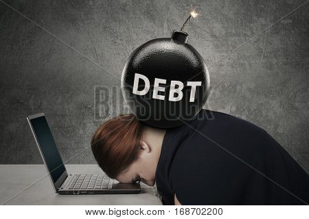 Young woman sleeping on the laptop with a text of debt on the bomb over her head