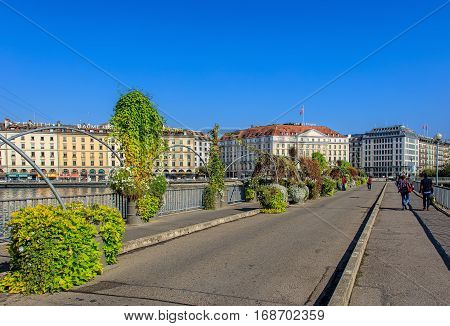 Geneva, Switzerland - 24 September, 2016: people on the Pont des Bergues bridge, buildings along the Rhone river. The city of Geneva is the capital of the Swiss Canton of Geneva, it is the second most populous city in Switzerland.