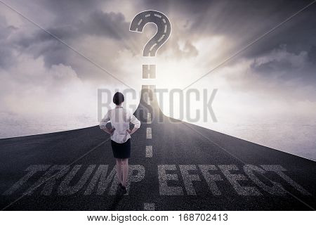Rear view of businesswoman standing on the highway with Trump Effect word and question mark