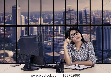 Portrait of young entrepreneur daydreaming while sitting in front of computer in the office
