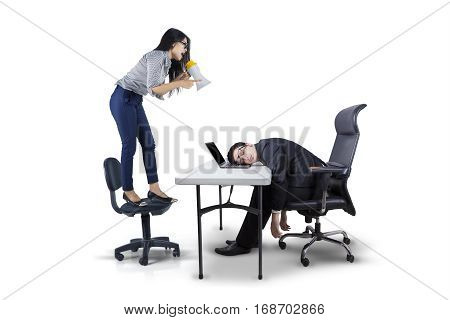 Picture of young leader shouting to her tired employee by using a megaphone isolated on white background