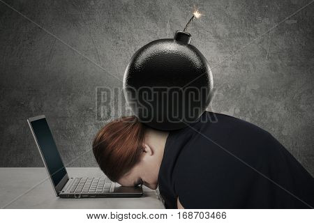 Young woman sleeping on the laptop while sitting in front of her desk with a bomb over her head