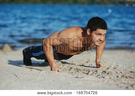 Strong attractive runner is pushed from the floor before morning jog