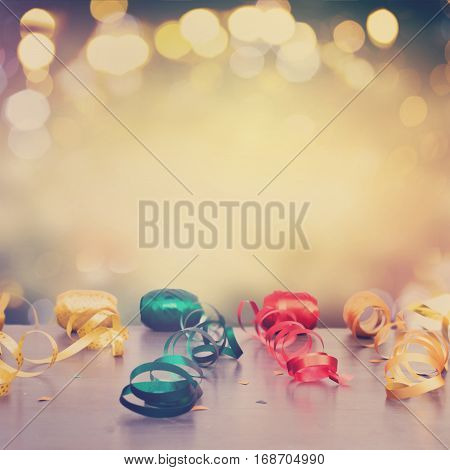 Carnaval festive curling paper decorations on dark wood border with copy space on bokeh festive background, retro toned