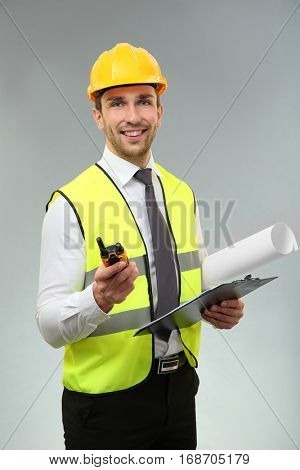 Handsome engineer with portable radio transmitter, drawing and clipboard on light background