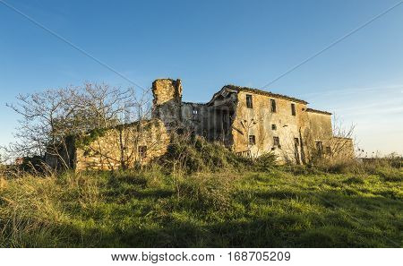 Old abandoned farmhouse in a meadow under blue sky