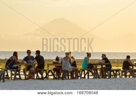Bali, Indonesia - June 14, 2015: Tourists in the restaurant on Gili Travangan island enjoying evening sunset view on Gunung Batur volcano on Bali, Indonesia.