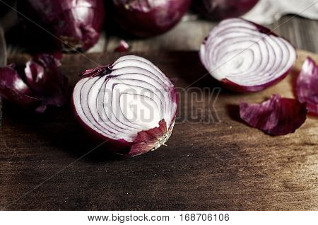 Red onions in the husk cut in half on a brown wooden chopping board close-up