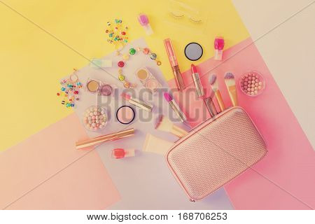 Colorful make up products with golden pursue pop art flat lay scene, retro toned