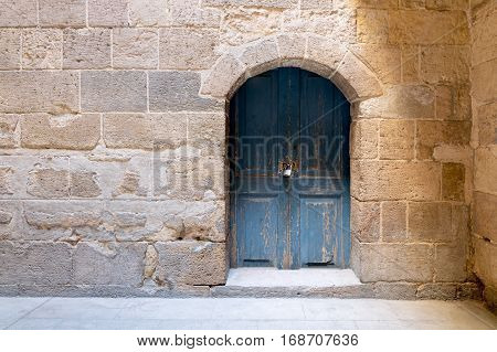 Blue wooden stained aged vaulted ornate door and stone wall Medieval Cairo Egypt