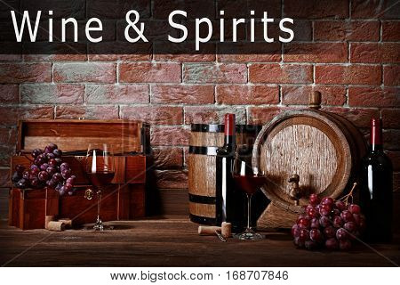Composition with wine and grape on wooden table. Text WINE AND SPIRITS on brick wall background