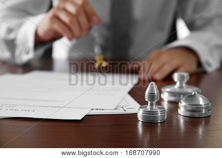 Metal stamps, papers and ink pad on notary public table