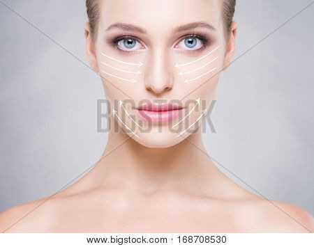 Portrait of attractive girl with beautiful blue eyes and arrows on face over grey background. Face lifting concept.