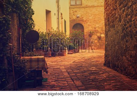 Empty street of small Tuscany town San Quirico d'Orcia in the morning fog, romantic travel vintage hipster european italy background