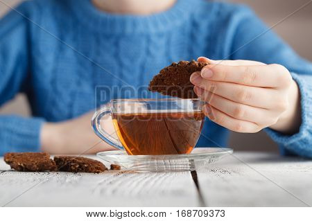 girl dunk biscuits in tea cup on table