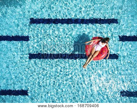 Woman relaxing on donut lilo in the pool water in hot sunny day. Summer holiday idyllic. Top view.