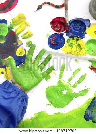 Closeup of boy's hand finger painting in art class