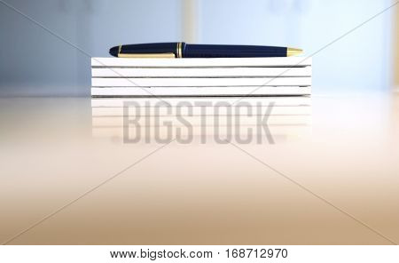 Stack of Notepads and a Pen