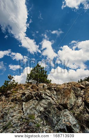 rocky mound and blue sky with clouds sunny summer day on mountain
