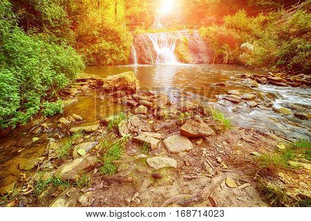 Beautiful sunny mountain rainforest waterfall with fast flowing water and rocks, long exposure. Natural seasonal travel outdoor background