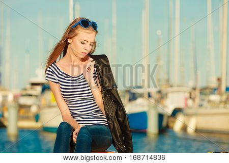 Tourism relax and people concept. Fashion blonde girl with blue heart shaped sunglasses in marina against yachts in port