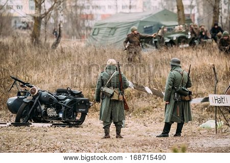 Gomel, Belarus - November 26, 2016: Two Unidentified Re-enactors Dressed As German Infantry Wehrmacht soldier at World War II are on patrol in autumn field.