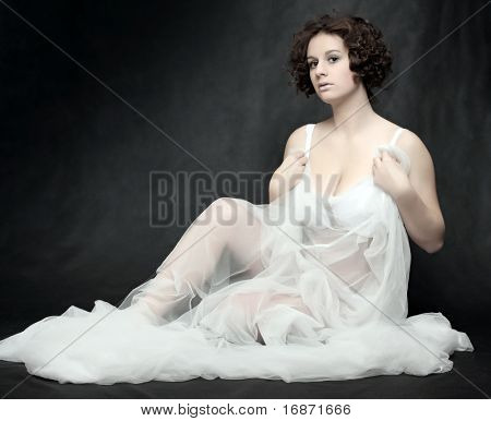 Beautiful slenderness young woman in bridal veil on black background. Low key studio shot. Great for calendar.