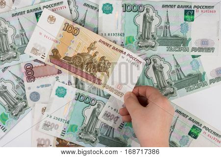Children's Hand Takes The Denomination From The Pile Of Randomly Scattered Russian Banknotes Of Diff