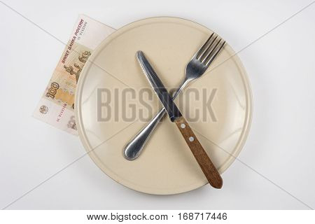 Empty Plate With Fork And Knife, Close Is A Hundred-ruble Note, White Background