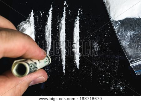 Drug Abuse. Hand of man holds rolled banknote for snorting line of cocaine powder. Problems with drugs concept. Top view.