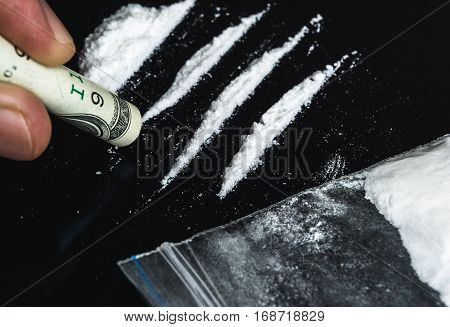 Hand of man holds rolled banknote for snorting line of cocaine powder. Problems with drugs concept