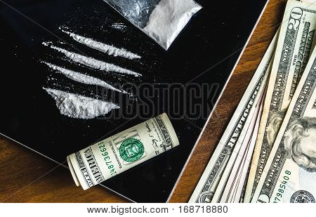 Lines of cocaine and some drugs pill in plastic packet, rolled dollar banknote on tablet and money cash on wooden table