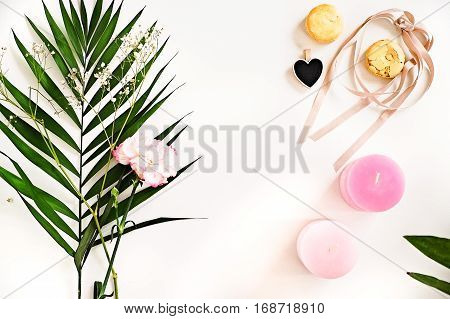 Beauty blogger flat lay on white. Green leaves and carnation flower pink ombre candles heart macaroons. Woman decorating ideas. Negative space for text