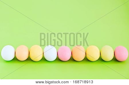 Flat lay row of colorful decorated eggs on a light green background. Pastel colors. Easter card. Negative space