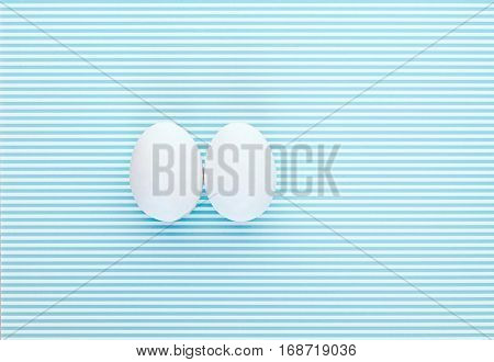 Two eggs on a colorful white and blue striped backdrop. Creative design minimal concept. Negative space