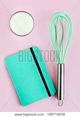 Colorful creative flat lay on a baby pink background. Still life styling. Neon greenery whisk notepad and glass of milk