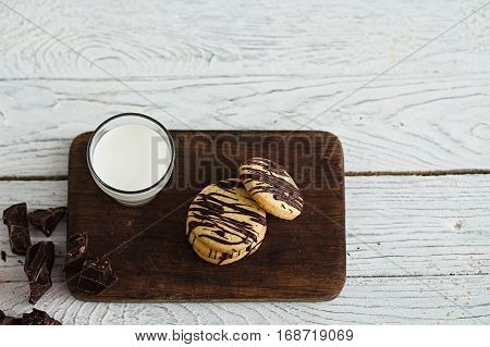 Glass of milk and shortbread butter cookies with chocolate drizzle. White wooden background. Minimalist food photography