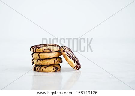 Stack of butter cookies with chocolate drizzle isolated on on a white background. Copyspace for text. Horizontal