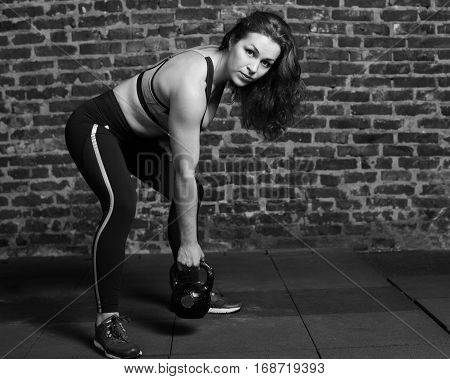 Young athletic woman lifting the kettlebell at the gym black and white