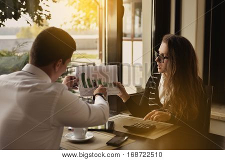 Two young business working on their laptop While sitting in a cafe Talking serious with work. Business life concept. portrait of two business people discussing new project in coffee shop. Close-up