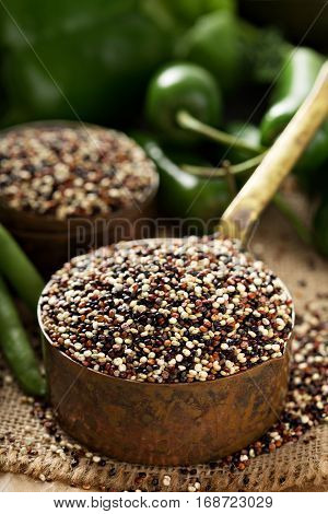 Dry quinoa in measuring cup and green vegetables, gluten free and healthy cooking concept