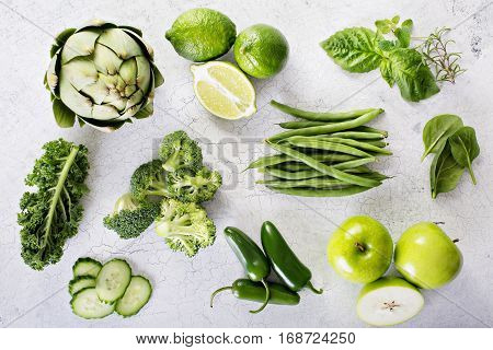 Variety of green vegetables and fruits flat layon the table