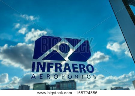 SAO PAULO BRAZIL - JANUARY 04 2017: Sticker of Infraero Aeroportos on the viewing glass on the background of blurry sunny blue sky with white clouds and buildings in Congonhas Airport