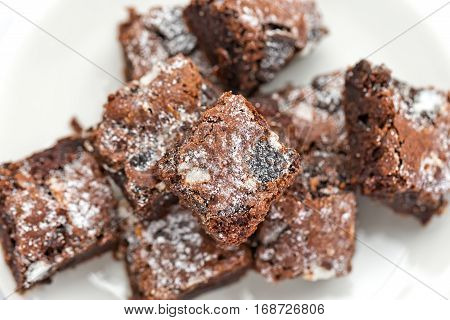 Delicious Freshly baked homemade cookies and cream brownie pieces on a white plate. Selective focus on the top of brownie