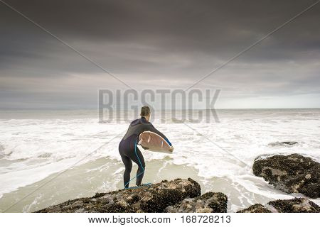 A surfer leaps in to the ocean with his surfboard under his arm at Jeffrey's Bay South Africa.