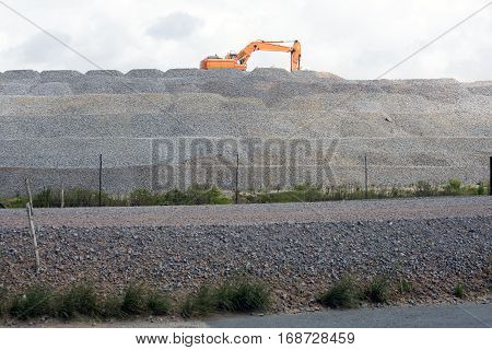 An excavator is loading on top of a mountain of stone material at a road building project.