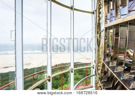 A view of the ocean through the glass winodws inside the light room of a lighthouse.